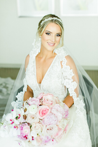 bride wearing a lace wedding gown with a deep V neckline, mantilla and crystal headband