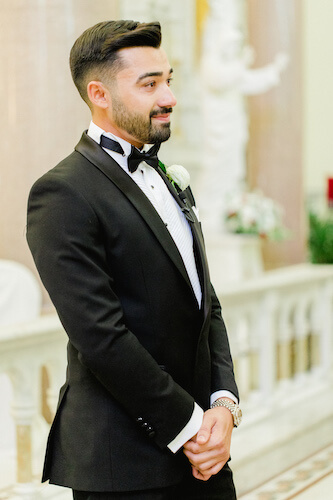 groom wearing a classic black tuxedo with wing tip collar black bow tie and white pocket square