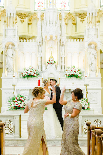 Mothers of the bride and groom high living in the middle of the aisle as their children marry