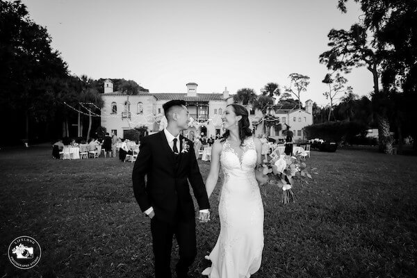 bride and groom walking across the lawn at their Powel Crosley wedding reception in Sarasota
