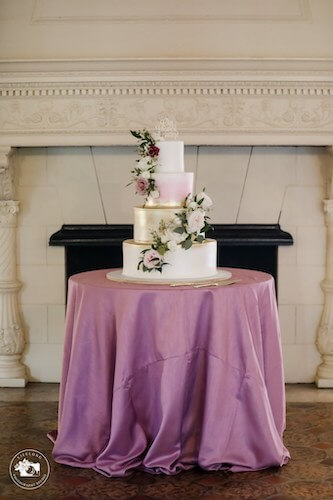 Pink white and gold wedding cake in front of the fireplace at Powel Crosley Estate in Sarasota