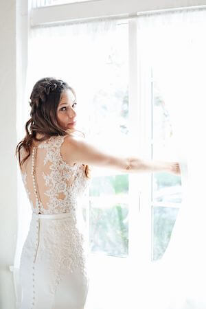 Bride in a lace wedding gown standing at the window