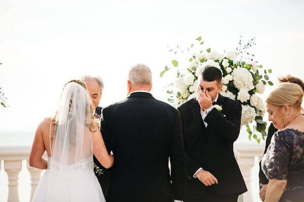 bride walking down the aisle to a tearful groom at the Hyatt Clearwater Beach
