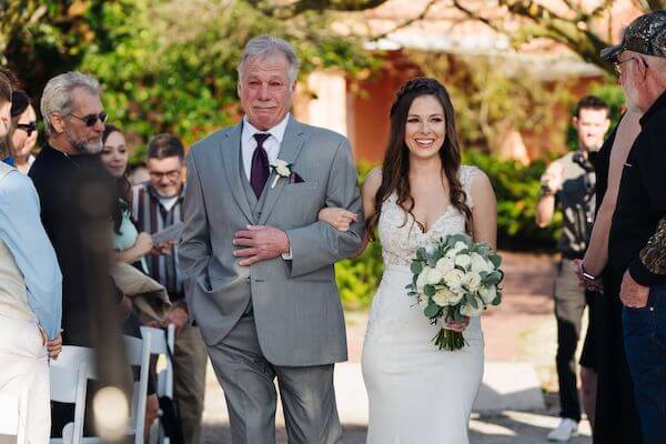 father of the bride crying as he escorts his daughter down the aisle at her wedding
