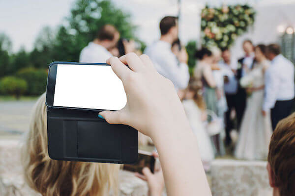 unplugged wedding with a guest taking a photo of the bride on their cell phone