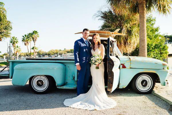 bride and groom standing next to a vintage pickup truck