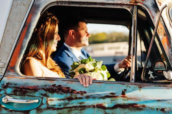 newlyweds taking photos inside a vintage pickup truck
