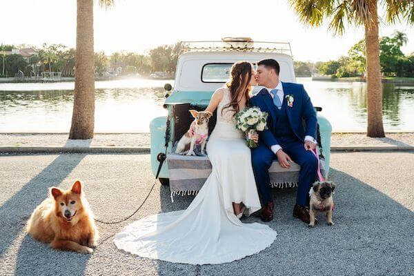 bride and groom taking photos with shelter puppies they brought to their wedding for people to adopt