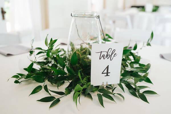 wedding centerpiece of greenery hurricane gloms and fairy lights