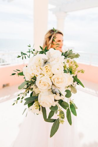 cascading white rose bouquet with greenery and dusty miller