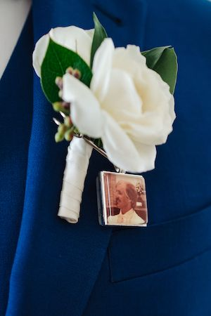 groom's white boutonniere with a memorial locket