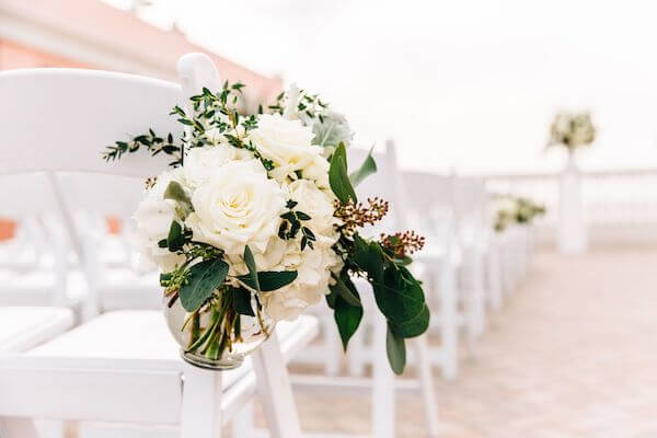 glass vases filled with white flowers on white garden chairs