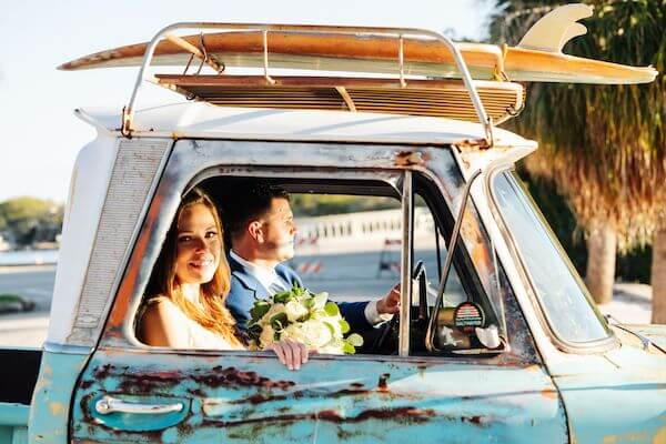 bride and groom riding in a vintage pickup truck