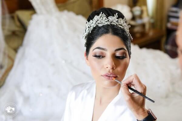 fairytale bride wearing tiara having lipstick applied