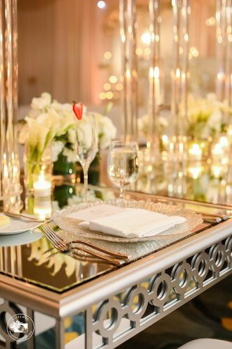 Fairytale wedding decor with mirrored tables, glass charger plates and white floral arrangements