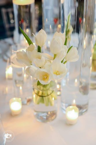 fairytale wedding reception with a vase of white tulips and votive candles