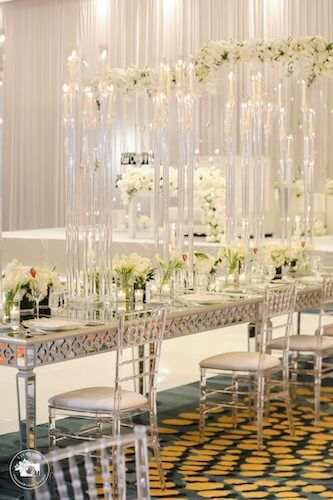 fairytale wedding reception with mirrored tables acrylic chivari chairs and white floral centerpieces