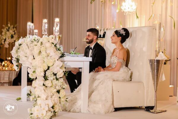 Newlyweds seated at their fairytale sweetheart table
