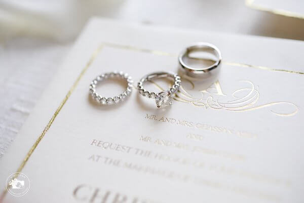 wedding and engagement rings sitting on a white and gold wedding invitation