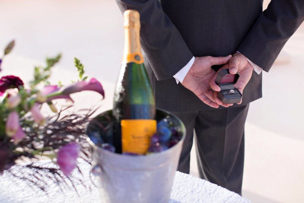 man holding an engagement ring behind his back ready for with a bottle of champagne and flowers next to him for the perfect proposal