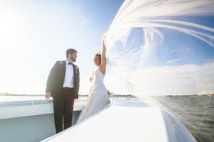 bride and groom on her families boat after their Saint Petersburg wedding
