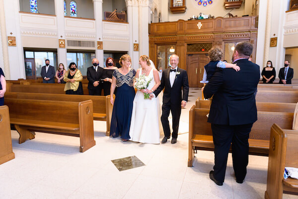 Saint Petersburg Florida bride walking down the aisle with her parents during an intimate wedding ceremony