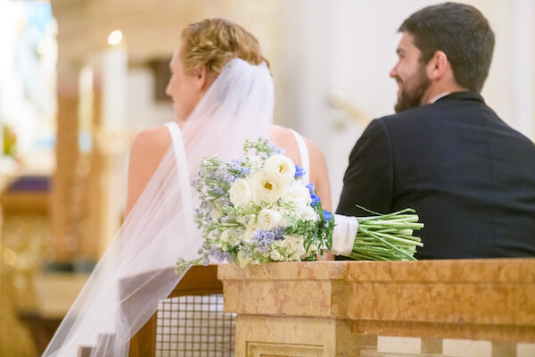 the back of a bride and groom with her blue and white bouquet resting behind them