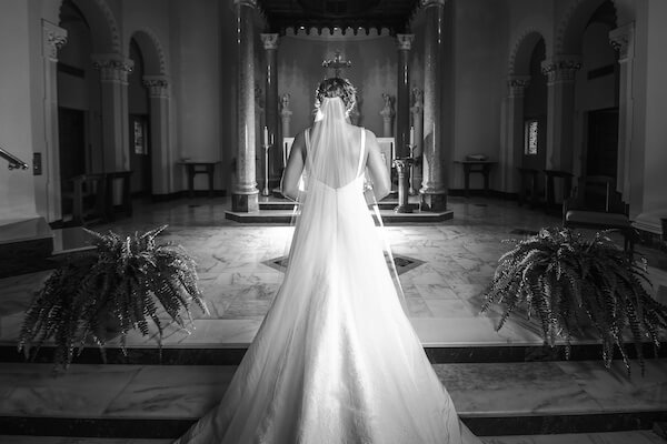 black and white photo from behind a bride standing at the altar