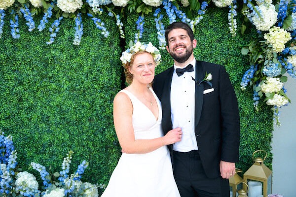 bride and groom in front of a boxwood headge wall decorated with blue and white flowers