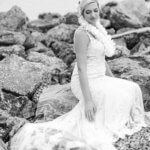 black and white photo of bride sitting on stone jetty ion Clearwater Beach