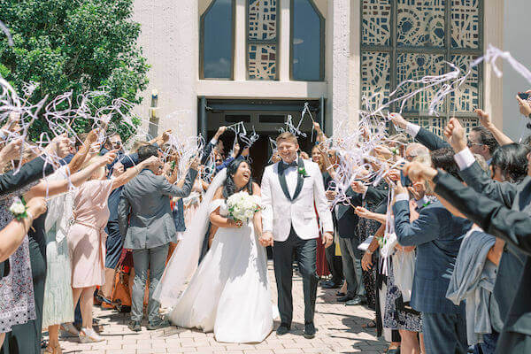 Tampa newlyweds being cheered on by wedding guests with white ribbon wands