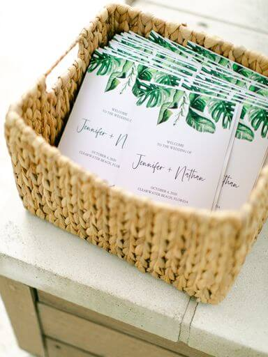 wedding programs decorated with tropical inspired greenery