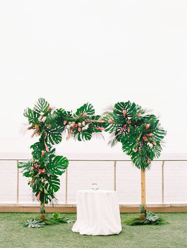 Hawaiian inspired wedding structure filled with greenery, tropical flowers and pineapple