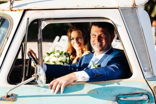 bride and groom looking out the window of a vintage teal pickup truck at their Saint Petersburg Florida wedding