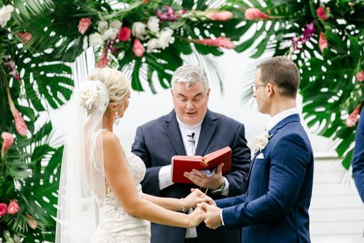 wedding officiant reading to a bride and groom in front of their Hawaiin inspired wedding structure of tropical flowers
