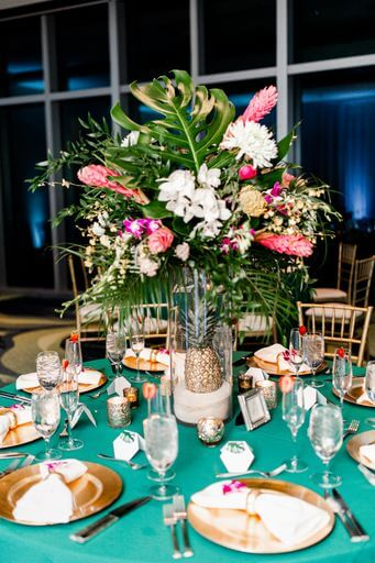 wedding reception set with teal linen, gold charger plates and tropical Hawaiian centerpieces