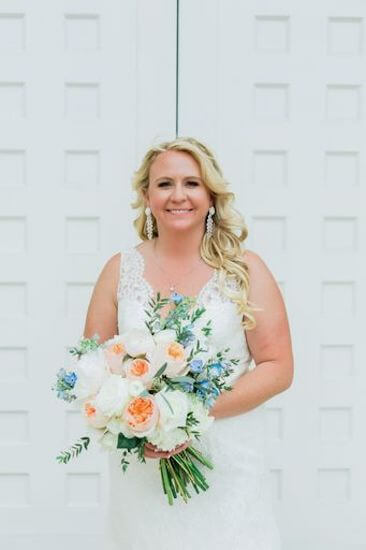 Destination wedding bride wearing a soft lace wedding gown with a coral and light blue bridal bouquet