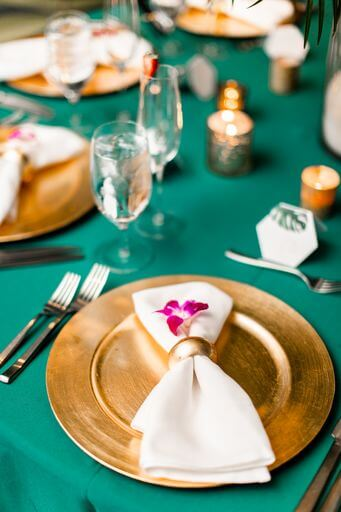 gold chargrrplates with white napkins and purple orchids