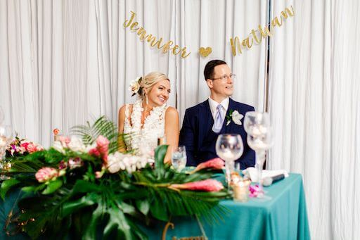 smiling newlyweds sitting at their Hawaiian inspired sweetheart table