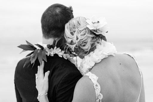 back and white photo taken from behind newlyweds wearing Hawaiian wedding leis