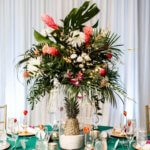 tropical themed wedding centerpieces with flowers and pineapples