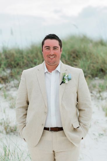 Groom wearing a light sand colored suit and open collar for his Clearwater Beach Destination wedding