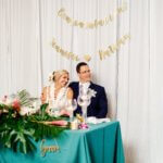 bride and groom sitting at their sweetheart table with teal linen and tropical flowers