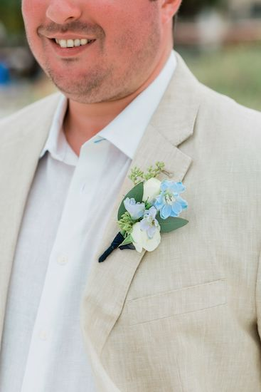 soft blue boutonniere with seeded eucalyptus on a sand colored suit for a destination wedding