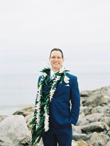 groom posing for photos on Clearwater Beach wearing a blue suit and traditional Hawaiian wedding lei