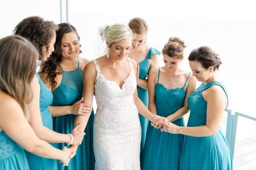 bridal party dressed in teal colored dresses praying over the bride