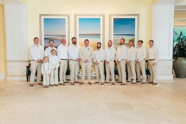 Groom and his groomsmen wearing sand colored slacks and casual white shirts paired with sandals for his Clearwater Beach wedding