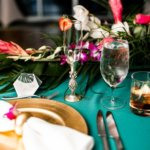 gold charger plate with napkin and tropical flowers