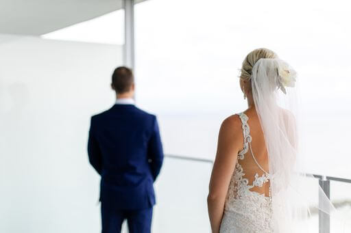 bride walking up behind her groom for their first look