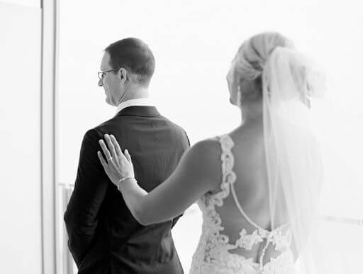 bride tapping her groom on the shoulder during their first look